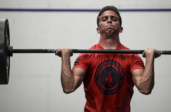 Senior Airman Frank Lopez, 56th Civil Engineer Squadron explosive ordinance team member, performs a barbell thruster during the 31 heroes competition held at Luke Air Force Base, Ariz., August 4, 2017. Lopez participated in the 31 heroes competition which honored the lives of 31 military members who lost their lives in a helicopter crash in Afghanistan in 2011. (U.S. Air Force photo/Airman 1st Class Caleb Worpel)