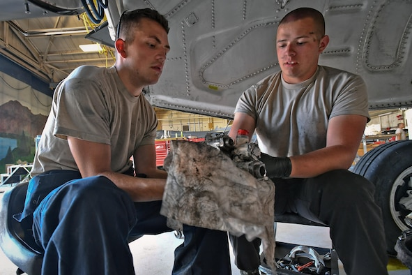 Airman 1st Class Dominic Haughian, left, and Airman 1st Class Nicholas Williams, both crew chiefs assigned to the 388th Maintenance Squadron, remove a hydraulic return manifold from an F-16 Fighting Falcon aircraft during phase maintenance at Hill Air Force Base, July 26. The jet is the last Hill AFB F-16 to go through phase at the base. After completing its phase inspection, this jet is scheduled for permanent transfer to Holloman AFB, New Mexico. (Paul Holcomb/U.S. Air Force)