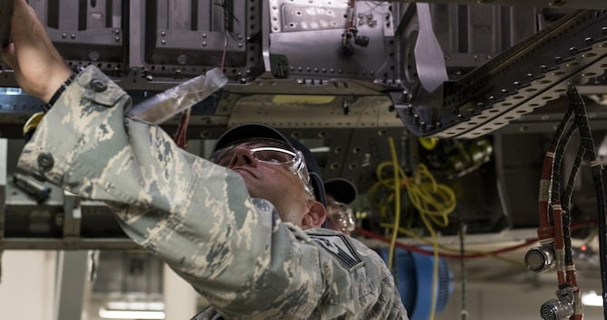 Senior Master Sgt. Travis Patterson, 389th Aircraft Mantenance Unit lead production superintendent, examines the underside of an unfinished F-15E Strike Eagle on the production floor of a defense contractor's factory in St. Louis, Mo, Aug. 3, 2017. The visit was an opportunity for Air Force members to see the beginning stages of products they deploy during the war on terrorism. (U.S. Air Force photo by Senior Airman Jeremy L. Mosier)