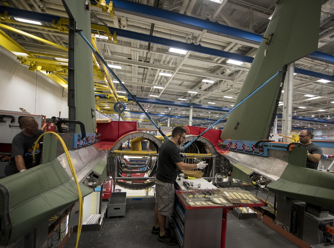 Defense contractor employees work on a portion of an F-15E Strike Eagle in a factory in St. Louis, Mo, Aug. 3, 2017. Workers were given the opportunity to meet with service members whom they produce products for. (U.S. Air Force photo by Senior Airman Jeremy L. Mosier)