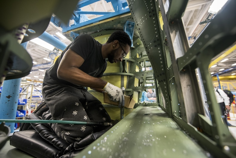 Orlando Dean, defense contractor assembly mechanic, looks over a portion of an F-15E Strike Eagle at a defense contractor's factory in St. Louis, Mo, Aug. 3, 2017. During the visit, military members were given the opportunity to meet those who create the products they use on a daily basis. (U.S. Air Force photo by Senior Airman Jeremy L. Mosier)