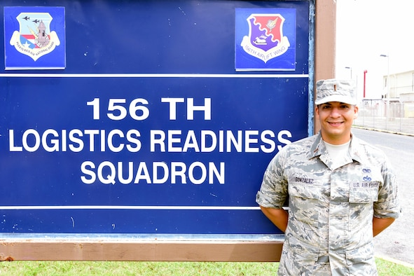 2nd Lt. Eduardo Gonzalez standing before the 156th Logistics Readiness Squadron sign.
