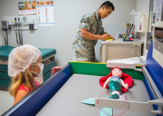 Airman First Class Nawym Meas, 96th Medical Group aerospace medical services apprentice, shows five-year-old Loralei Gill, how to take medical measurements during the first Teddy Bear Clinic at Eglin Air Force Base, Aug. 4. Children took their stuffed animals and characters through eight clinic stations. Stations included registration, CPR, immunizations, nutrition, fitness and vital signs. The Pediatric Clinic hosted 127 children to educate them about hospital procedures and to demonstrate what they may expect if they need to see a doctor. (U.S. Air Force photo/Ilka Cole)