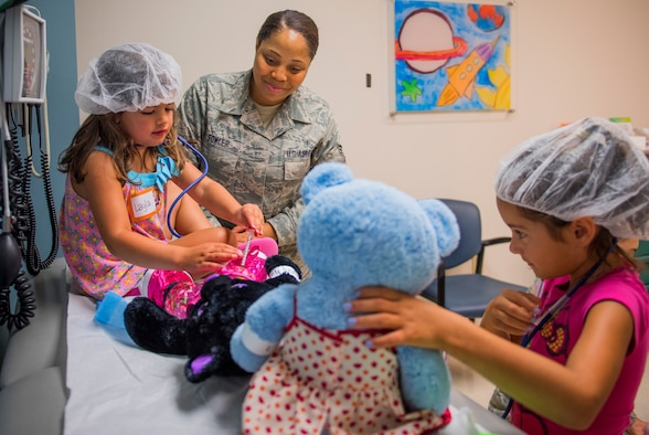 Senior Airman Antoinette Fowler, a 96th Medical Group aerospace medical services journeyman, shows four-year-old, Layla Sherwood how to give an immunization during the first Teddy Bear Clinic at Eglin Air Force Base, Aug. 4. Children took their stuffed animals and characters through eight clinic stations. Stations included registration, CPR, immunizations, nutrition, fitness and vital signs. The Pediatric Clinic hosted 127 children to educate them about hospital procedures and to demonstrate what they may expect if they need to see a doctor. (U.S. Air Force photo/Ilka Cole)