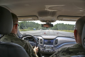 Two soldiers drive in a car on a course with cones on the road.