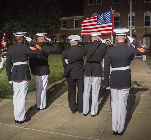 "Marines of the parade staff, the guest of honor, and hosting official render honors to the National Ensign as a part of ""pass and review"" during the Staff Noncommissioned Officer Evening Parade at the Barracks, Aug. 4, 2017. The guest of honor for the parade was retired Marine Corps Col. Archie Simpson, Guadalcanal veteran, and the hosting official was Lt. Gen. James B. Laster, director, Marine Corps Staff. (Official Marine Corps photo by Cpl. Robert Knapp/Released)"