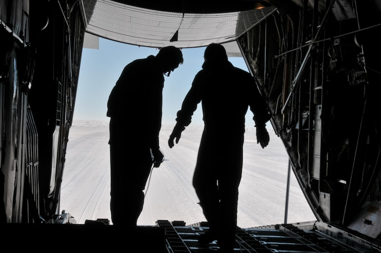 Master Sgt. Randy Powell (left) and Airman 1st Class Jason Vannostrand conduct a combat offload from an LC-130 aircraft here July 28, 2017. Powell is an instructor loadmaster with the 139th Airlift Squadron, and Vannostrand is a student loadmaster with the squadron. Raven Camp is used to train aircrews on LC-130 operations on snow runways. (U.S. Air National Guard photo by Master Sgt. Catharine Schmidt/Released)