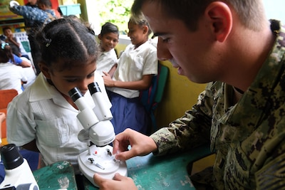 Navy Lt. j.g. Jack Dembowski helps a girl examine a specimen through a microscope during an entomology class at República de Colombia Elementary School in Silin, Honduras, Aug. 1, 2017. Sailors participated in a community relations project as part of Southern Partnership Station 2017, a U.S. Navy deployment focused on subject-matter-expert exchanges with partner-nation militaries and security forces in Central and South America. Navy photo by Petty Officer 1st Class Jeremy Starr