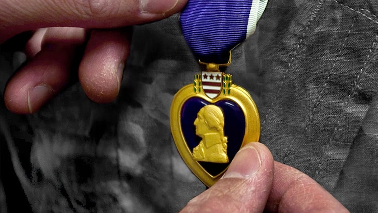 A person holds a Purple Heart medal next to a military uniform.
