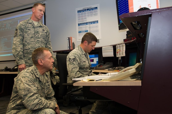 During a tour of the 310th Space Wing, Lt. Gen. David J. Buck, Commander, 14th Air Force (Air Forces Strategic), Air Force Space Command; and Commander, Joint Functional Component Command for Space, U.S. Strategic Command, stops to observe Staff Sgt. Jacob Janisch, 6th Space Operations Squadron, hard at work