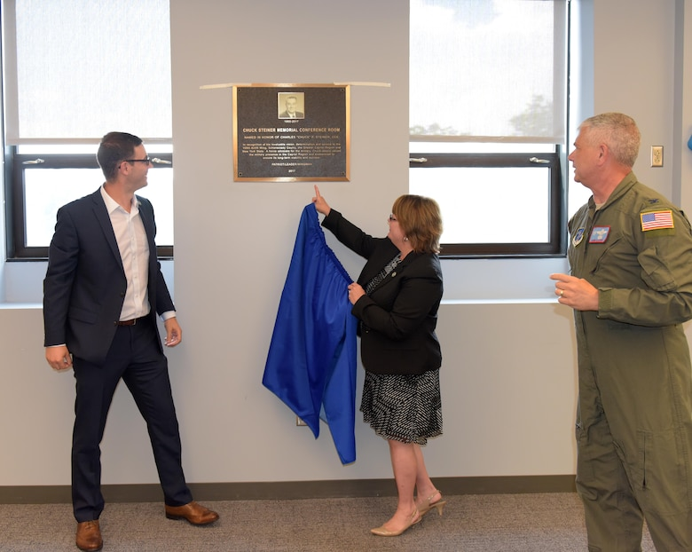 """Marcy and Matt Steiner unveil the """"Chuck Steiner Memorial Conference Room"""" plaque in the 109th Airlift Wing's new wing conference room at Stratton Air National Guard Base, Scotia, New York, as Col. Shawn Clouthier, 109th AW commander, looks on during a dedication ceremony to Chuck Steiner on Aug. 4, 2017. (U.S. Air National Guard photo by Senior Master Sgt. William Gizara/Released)"""