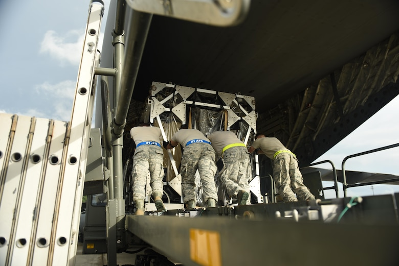 Loadmasters loading a TIS onto a C-17