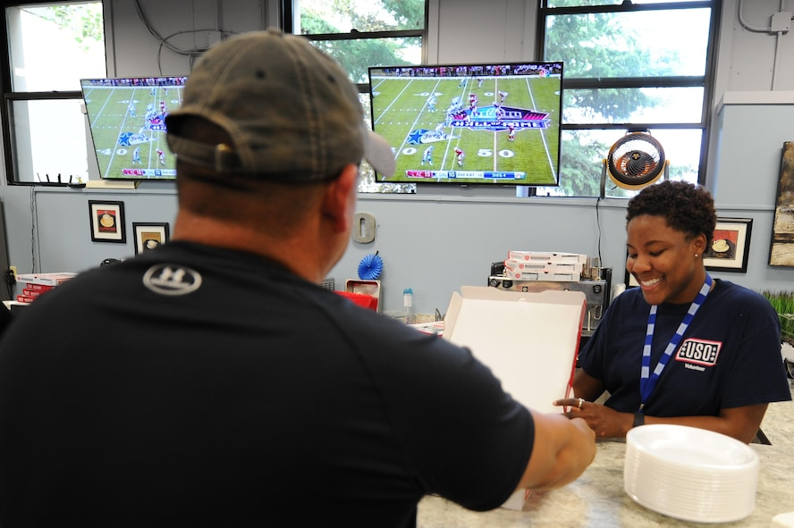 U.S. Air Force Senior Airman Kahdija Slaughter, a 354th Fighter Wing Public Affairs broadcast journalist and USO volunteer, serves a visiting service member a slice of pizza Aug. 3, 2017, at Eielson Air Force Base, Alaska. The USO opened for the Pro Football Hall of Fame Game 2017 and provided free pizza. (U.S. Air Force photo by Airman 1st Class Eric M. Fisher)