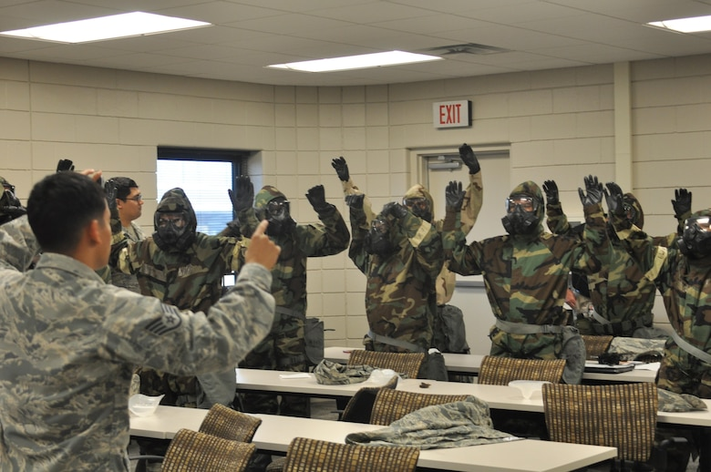 "301st Fighter Wing Mission Support Group Airmen raised their hands for inspection after ""suiting-up"" and checking their wingman's Mission Oriented Protective Posture (MOPP) gear during Ability to Survive and Operate (ATSO) training Saturday, Aug. 5, 2017 at Naval Air Station Fort Worth Joint Reserve Base, Texas. Annual exercises hone Airmen's skills to continue executing the mission in austere conditions. (U.S. Air Force photo/ Tech. Sgt. Charles Taylor)"