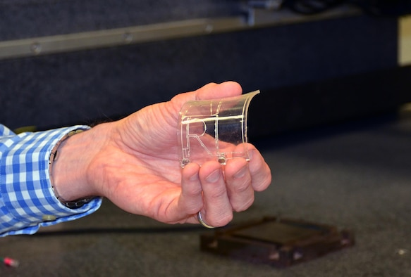 A member of the Flexible Materials and Processes team at the Air Force Research Laboratory's Materials and Manufacturing Directorate exhibits an additively manufactured electrical circuit embedded in a flexible material substrate. The flex team is exploring novel ways to use 3-D printing technology to create next generation flexible hybrid technologies for the Air Force.  (U.S. Air Force photo / Marisa Alia-Novobilski)