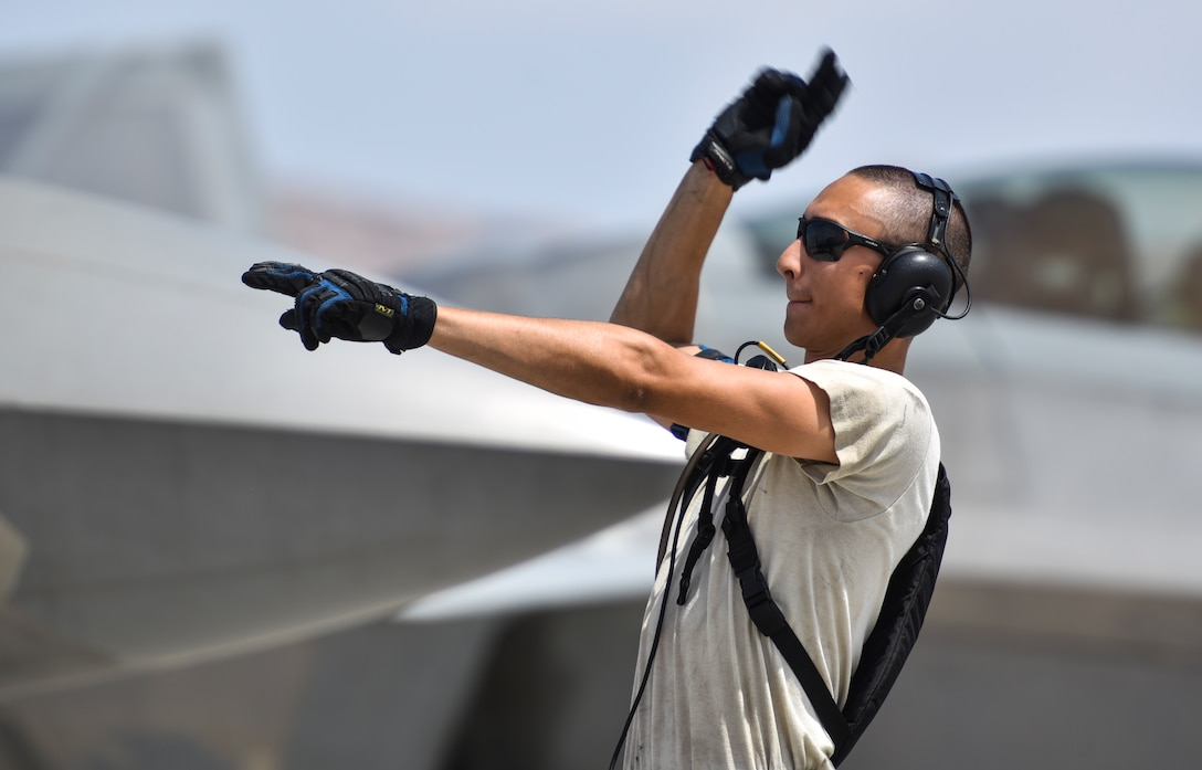 U.S. Air Force Airman 1st Class Steven Covington, crew chief from the 325th Aircraft Maintenance Squadron, Tyndall Air Force Base, Fla., signals an aircraft to begin moving on the flightline at Nellis Air Force Base, Nev., during Red Flag 17-3, July 18, 2017. Covington and other crew chiefs are responsible for preparing the jet before takeoff.