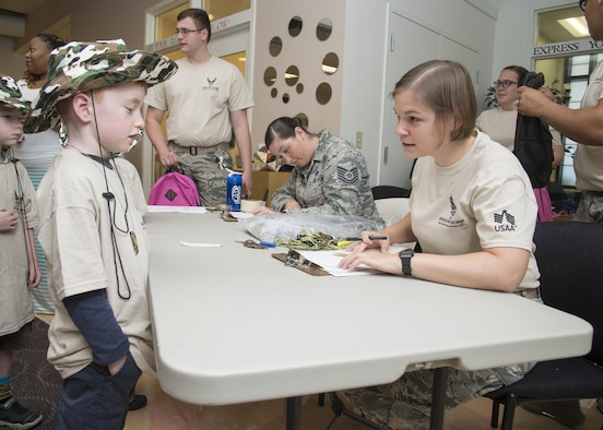 """Gunner Conn, talks with 2nd Lt. Katherine Vaughn, 436th Airlift Wing Public Affairs officer, during Kids Understanding Deployment Operations Aug. 3, 2017, at the Youth Center on Dover Air Force Base, Del. Children were given """"deployment"""" back packs and were taught about the different parts of deployment their parents go through.  (U.S. Air Force photo by Staff Sgt. Jared Duhon)"""