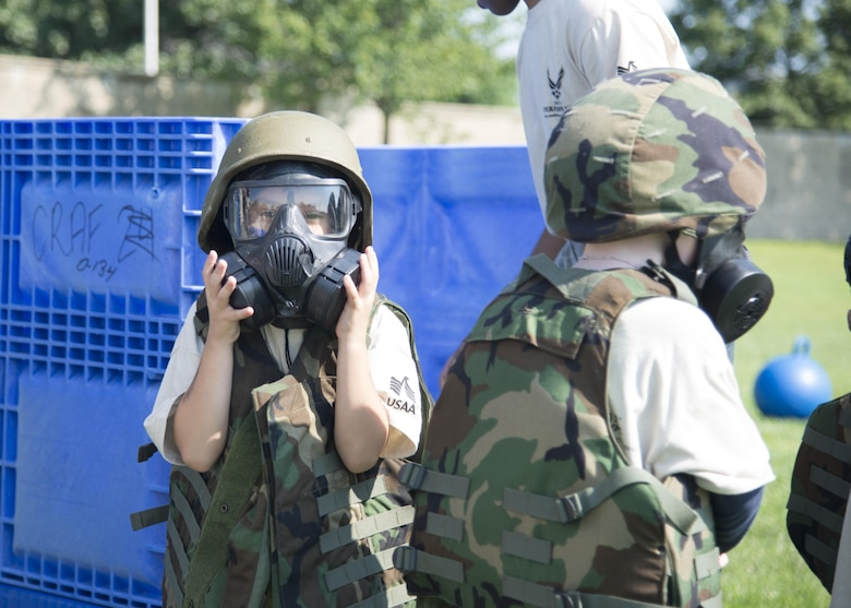 A child dressed in a gas mask and body armor checks his seal during the Kids Understanding Deployment Operations Aug. 3, 2017, at the Youth Center on Dover Air Force Base, Del. Gear was brought out by various base organizations to help children understand what their parents might experience during a deployment. (U.S. Air Force photo by Staff Sgt. Jared Duhon)