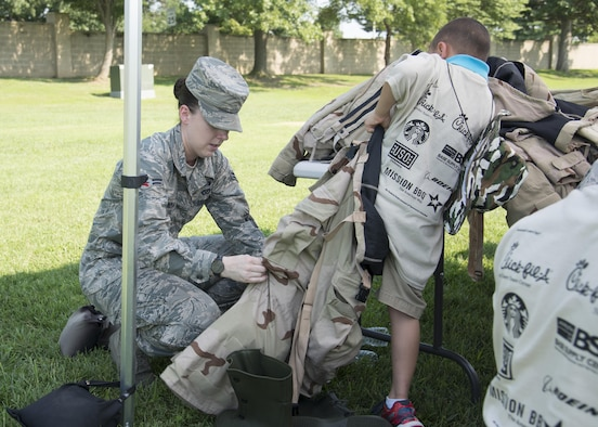Airman 1st Class Marnie Wickman, 436th Civil Engineer Squadron emergency management, helps a child with chemical gear during Kids Understanding Deployment Operations Aug. 3, 2017, at the Youth Center on Dover Air Force Base, Del. During KUDOs, children were able to try on different pieces of equipment and learn about the deployment process. (U.S. Air Force photo by Staff Sgt. Jared Duhon)