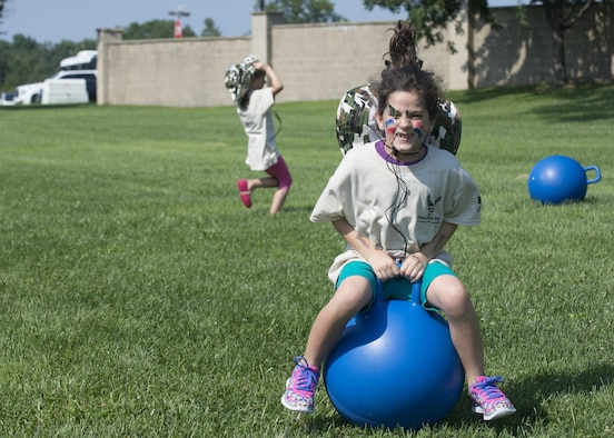 Leah Porreca, a child with the Youth Center, races to the finish line on a ball during Kids Understanding Deployment Operations Aug. 3, 2017, at the Youth Center on Dover Air Force Base, Del. The event sends kids through a simulated deployment processing line, obstacle course and other educational stations to give them a perspective on how military members prepare and process to deploy. (U.S. Air Force photo by Staff Sgt. Jared Duhon)