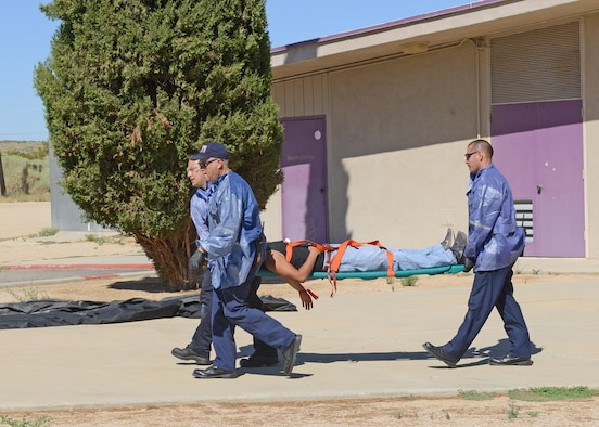 Members of the Edwards AFB Fire Department transport a simulated gunshot victim to a triage area outside the Scorpatorium at Desert High School during Exercise Desert Wind 17-04 Aug. 7. (U.S. Air Force photo by Kenji Thuloweit)