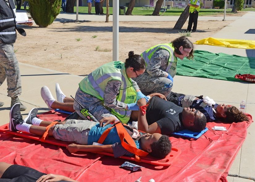 Simulated gunshot victims are treated at a makeshift triage area outside the Scorpatorium multipurpose room at Desert High School by 412th Medical Group personnel Aug. 7. (U.S. Air Force photo by Kenji Thuloweit)