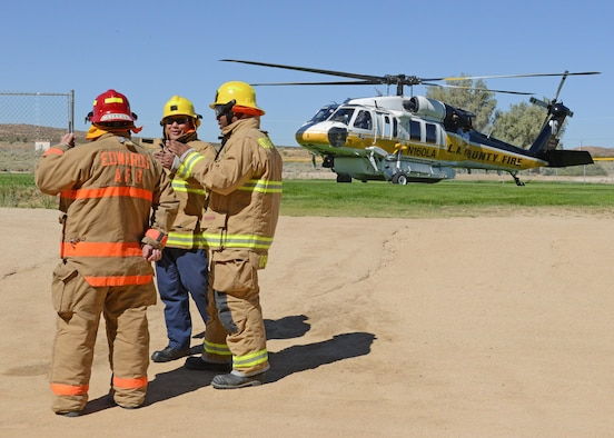 Members of the Edwards AFB Fire Department stand by a Los Angeles County Fire Department Firehawk helicopter that landed on a Desert High School sports field to participate in Exercise Desert Wind 17-04 held Aug. 7. (U.S. Air Force photo by Kenji Thuloweit)