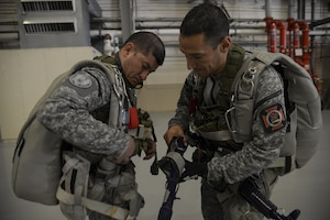 Colombian Air Force members, suit-up for a multinational personnel airdrop from a Colombian 295 aircraft in a during Exercise Mobility Guardian at Joint Base Lewis-McChord, Wash., Aug. 6, 2017. Nineteen multinational service members from Colombia, France and Pakistan jumped out of the Casa 295 at Larson, Wash. (U.S. Air Force photo by Staff Sgt. Angela Ruiz)