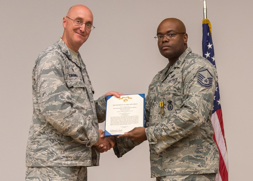 Col. George Tromba, 412th Mission Support Group commander, presents Master Sgt. Maurice Lucas II, 412th Security Forces Squadron, with the Air Force Commendation Medal (third oak leaf cluster) during a commander's call Aug. 2 at the Edwards Air Force Base, Calif., base theater. (U.S. Air Force photo/Kyle Larson)