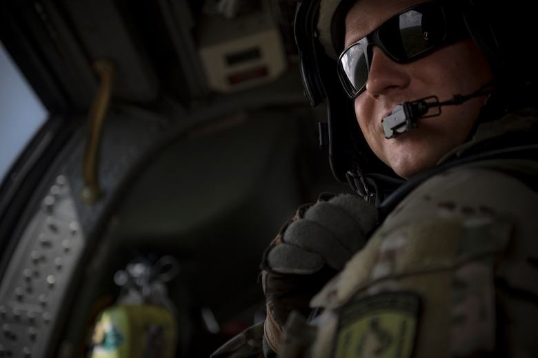 Master Sgt. Zachary Ferguson, 41st Rescue Squadron special missions aviator, rides in the back of an HH-60G Pave Hawk, 7 Aug. 2017, near Dog Island, Fla.