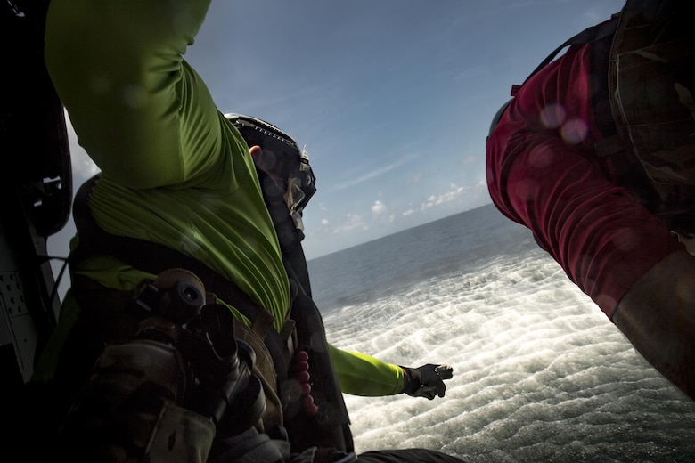 Staff Sgt. Robert, 38th Rescue Squadron pararescueman, directs a fellow PJ to jump into the water, Aug. 7, 2017, near Dog Island, Fla.