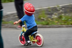 Maddox Neff, 2, pushes himself on his bike as spectators await the return of cyclists during the Moose Run time-trial race at Joint Base Elmendorf-Richardson, Alaska, Aug. 3, 2017. For more than 15 years, the club has hosted road race events at JBER.