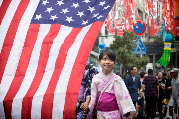 A girl wearing a traditional Yukata walks on a street decorated with mixture of American and Japanese ornaments during the 67th Annual Tanabata Festival in Fussa City, Japan, Aug. 4, 2017. This year's festival theme is Fussa City uniquely integrated with an international and American culture. (U.S. Air Force photo by Yasuo Osakabe)
