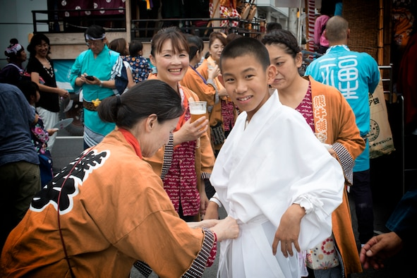 A lady from the Kumaushi Hayashi tightens a boys belt during the 67th Annual Fussa Tanabata Festival at Fussa City, Japan, Aug. 4, 2017. Ohayashi is a Japanese traditional play which roused the movement of the festival car. The festival car featured traditional Japanese characters such as the fox and oni, a Japanese demon, as part of the festivities. (U.S. Air Force photo by Yasuo Osakabe)