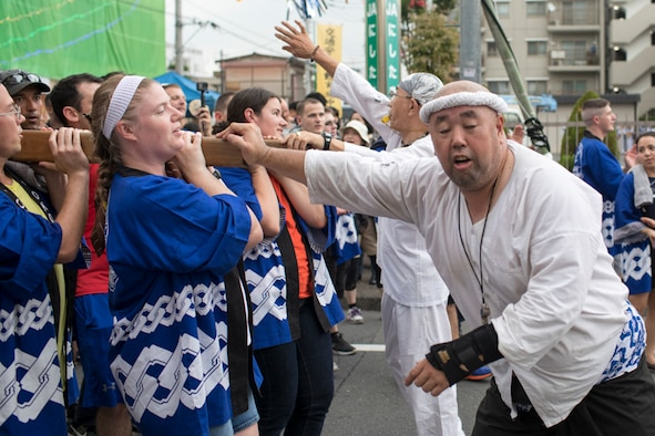 Mikoshi guides push back the wing mikoshi during the 67th Annual Fussa Tanabata Festival at Fussa City, Japan, Aug. 4, 2017. More than 80 Airmen participated in the ceremonial opening parade, taking turns as they carried a mikoshi, or portable shrine, on their shoulders through the streets of Fussa. (U.S. Air Force photo by Yasuo Osakabe)