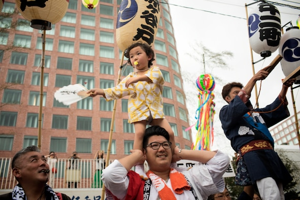 A child helps direct people carrying a mikoshi, or portable shirine, in the 67th Annual Fussa Tanabata Festival at Fussa City, Japan, Aug. 4, 2017.  At many points during the mikoshi parade, the various groups carrying mikoshi would raise the shrines. (U.S. Air Force photo by Yasuo Osakabe)