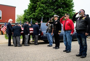 Honorary pallbearers from the Emmons American Legion move Navy Fireman 3rd Class Glaydon I.C. Iverson's casket from the hearse to Emmons (Minnesota) Lutheran Church  as members of honor detail and military veterans stand at attention May 27, 2017.
