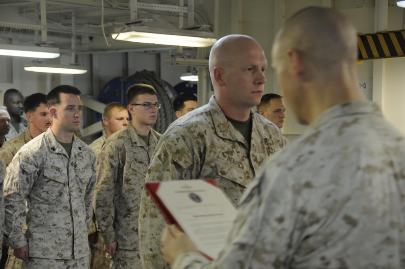 Marine Corps Capt. Dakota Herpich, center, is promoted to his current rank while deployed with the 24th Marine Expeditionary Unit serving aboard the amphibious assault ship USS Bataan, July 1, 2017. Herpich is the officer in charge of the unit's law enforcement detachment. Marine Corps photo by Capt. Jordan Cochran