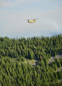 An Oregon Army National Guard CH-47 Chinook helicopter with 1st Battalion, 168th Aviation Regiment carries a 2,000-gallon capacity water bucket above the Mt. Jefferson Wilderness Area in order to support firefighting efforts on the Whitewater Fire on Aug. 5, 2017. The Oregon National Guard was called upon following Gov. Kate Brown's emergency order on Aug. 2. Two Chinook helicopters are currently assigned to the fire.