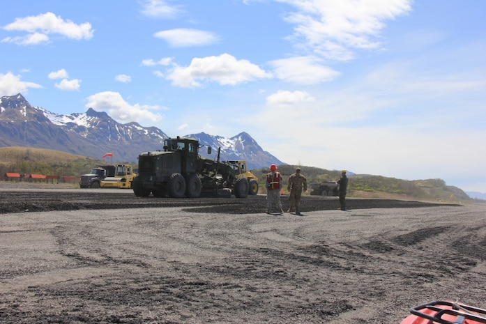 Reserve Marine and Army personnel oversee the extension of a runway during Integrated Readiness Training Old Harbor, June 1, 2017, in Old Harbor, Alaska. Marine Aircraft Group 41, 4th Marine Aircraft Wing, Marine Forces Reserve, led exercise IRT Old Harbor during which service members trained in a wide variety of skills while extending Old Harbor's runway from 2,700 feet to 4,700 feet helping facilitate economic development.
