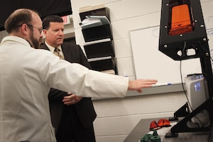 Dr. Sam Emery, a research physicist at NSWC Indian Head EOD Technology Division, discusses the command's ability to design and produce energetic materials by way of additive manufacturing with NAVSEA Executive Director James Smerchansky during his Aug. 1 visit.
