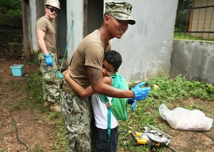 A U.S. Navy Sailor hugs a Honduran student during a Southern Partnership Station 17 community relations project at a local elementary school.