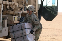A Soldier assigned to 215th Brigade Support Battalion, 3rd Armored Brigade Combat Team, 1st Cavalry Division recovers one of two bundles off of the drop zone during air drop resupply training July 27, 2017 at Udairi Range Complex, Kuwait. The Soldiers were evaluated on their execution of a tactical convoy, drop zone set-up and marking, drop zone security, and resupply recovery. (U.S. Army photo by Staff Sgt. Leah R. Kilpatrick))