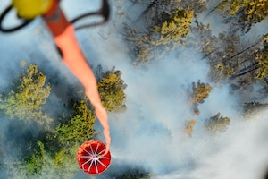 An Army helicopter dumps water on a wildfire.