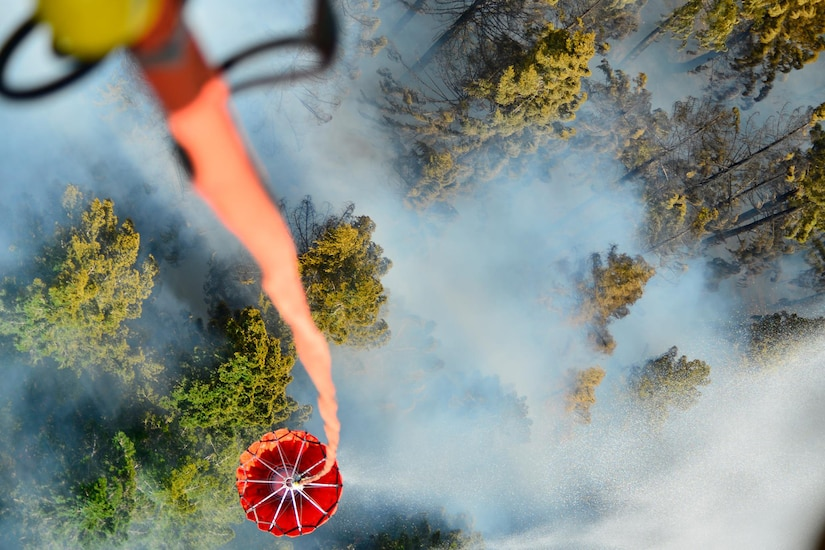 A bambi bucket dumps water on a wildfire.