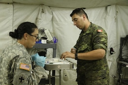 345th Combat Support Hospital medic, U.S. Army Spc. Stephanie Orta (left) and Canadian medic from the 35th Field Ambulance unit, Cpl. Nick Kennedy (right) , quickly prepare the emergency room with new syringes and other medical items before receiving patients.  For three weeks, Orta and Kennedy, along with other joint military service members worked alongside each other in the 345th CSHwithin the combined joint operating area in the notional country of Atropia during the Global Medic Combat Support Training Exercise (CSTX) at Fort Hunter Liggett, Calif.  345th CSH, apart of the 332nd Medical Brigade, 3d Medical Command (Deployment Support), participated in the event as the premier health support provider to the combined joint task force that included military members from the U.S. Army Guard Reserve (AGR) and Army Reserve, Navy, Air Force, Marines, along with medical professionals from the Canadian Army and Royal Kingdom of Saudi Arabia.  The full range of medical capabilities support provided by the Joint Task Force honed skills in providing medical services such as ambulatory care, medical evacuation, emergency room triage and treatment, x-ray, laboratory and dental services, preventive medicine, advanced trauma management, pharmacy, and clinical services.  Global Medic is a situational scenario-based simulation exercise focused on the development of 80% strategic/operational and 20% joint medical and tactical skills and is held simultaneously at various locations from Shaw Air Force Base, S.C., to Fort Devens, Mass., Fort Hunter Liggett, Calif., Camp Roberts and Camp Parks, Calif.