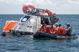 This is an image of a floating NASA spacecraft with a group of astronauts in a boat.