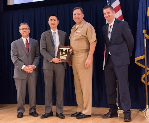 Ji Kim, deputy comptroller for Carderocks budget office, receives the Rear Adm. Grace M. Hopper Award for excellence in organizational support at the Naval Surface Warfare Center, Carderock Division Honor Awards ceremony Aug. 1, 2017, in West Bethesda, Md. From left to right: Technical Director Dr. Tim Arcano, Kim, Commanding Officer Capt. Mark Vandroff and Comptroller Eric Stone. (U.S. Navy photo by Jake Cirksena/Released)