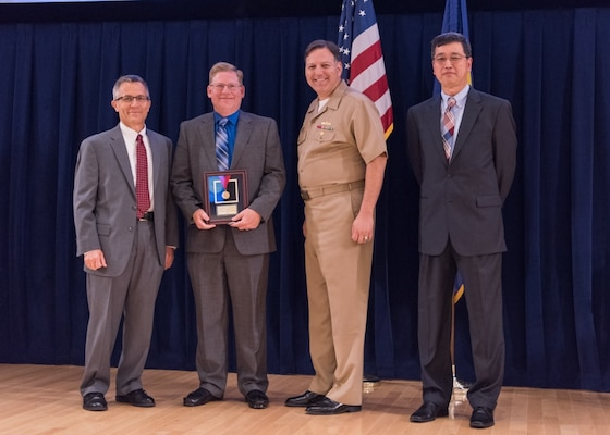 Richard Loeffler, the program manager for advanced signature guidance and training systems, receives the Capt. Harold E. Saunders Award for exemplary technical management at the Naval Surface Warfare Center, Carderock Division Honor Awards ceremony Aug. 1, 2017, in West Bethesda, Md. From left to right: Technical Director Dr. Tim Arcano, Loeffler, Commanding Officer Capt. Mark Vandroff and Ship Signatures Department Head Dr. Paul Shang. (U.S. Navy photo by Jake Cirksena/Released)