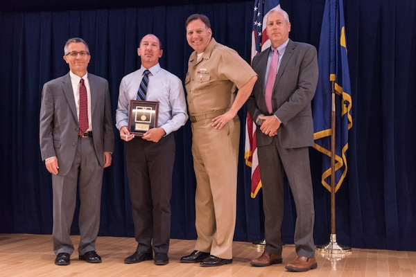 Lawrence Michelon, a senior electronics engineer for the Systems Design and Integration Branch at Carderock™s Combatant Craft Division in Norfolk, receives the Rear Adm. George W. Melville Award for engineering excellence at the Naval Surface Warfare Center, Carderock Division Honor Awards ceremony Aug. 1, 2017, in West Bethesda, Md. From left to right: Technical Director Dr. Tim Arcano, Michelon, Commanding Officer Capt. Mark Vandroff and Naval Architecture and Engineering Department Head Mike Brown. (U.S. Navy photo by Jake Cirksena/Released)